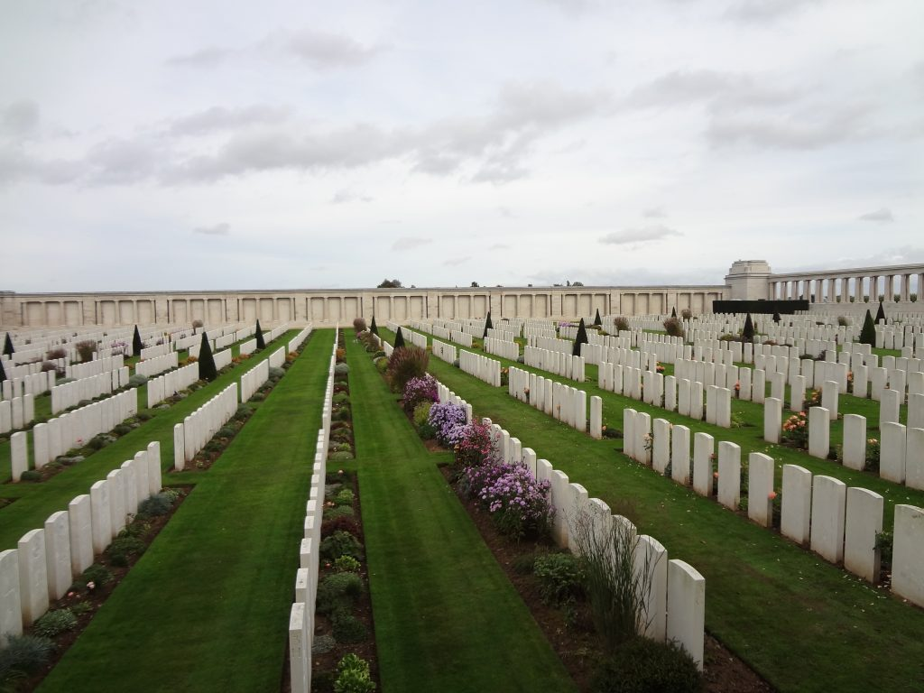 A large walled military cemetery located near Pozières on the Somme, France, showing the white headstones common to Commonwealth War Graves Commission cemeteries.