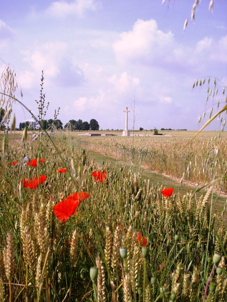 Depicts a small military cemetery near the Bullecourt battlefield of 1917, with the Remembrance cross in the background, and red poppies in foreground