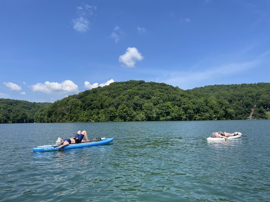 Blue lake with two White women lying down on their paddle board under a blue sky.