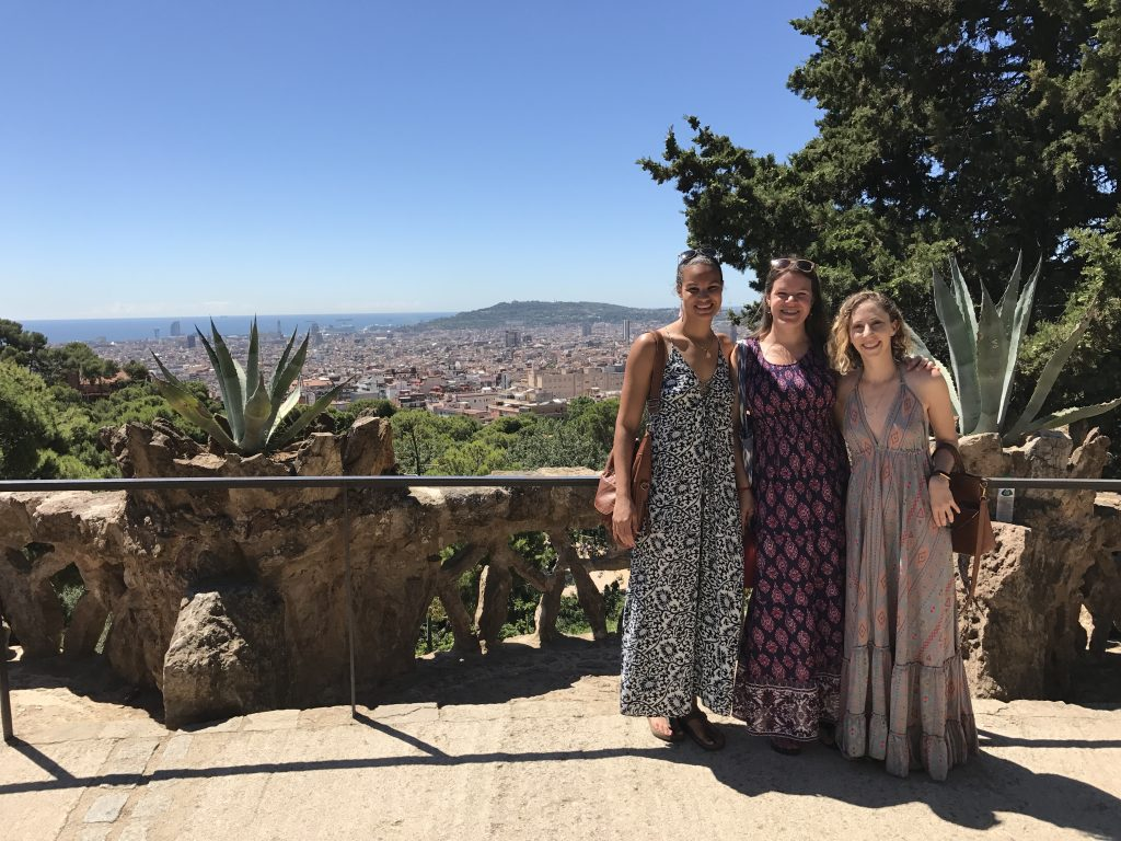 Three women in long dresses posing for the camera with a cityscape backdrop of Barcelona