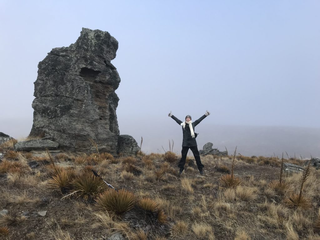 A White woman jumping in the air with her arms up while surrounded by wild grass and a large rock in the background