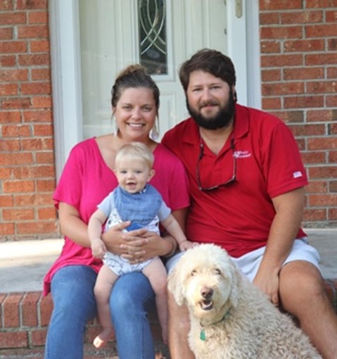 Photo of Emily Yeager with her husband, son, and dog.