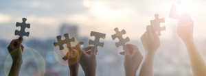Image of hands holding up jigsaw puzzle pieces